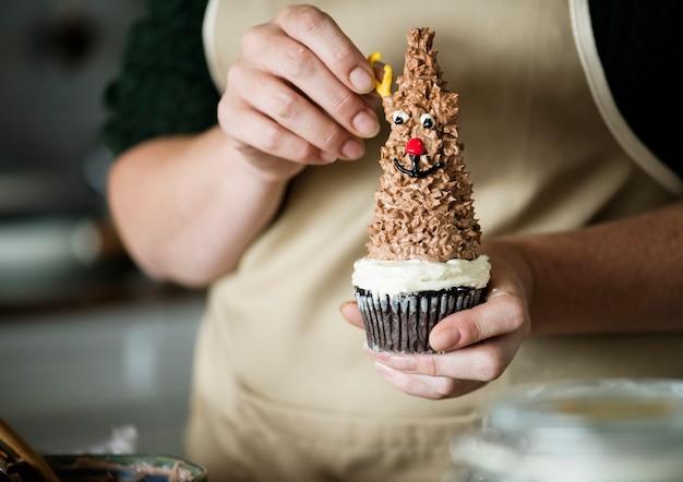 Vrouw die geweitakken op een rendier zetten cupcake