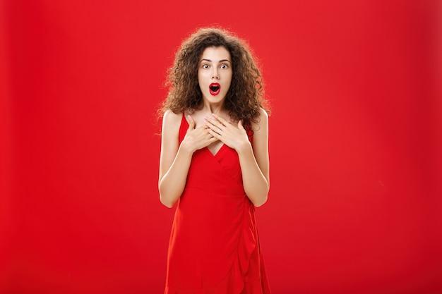 Vrouw die geweldig nieuws ontvangt, is onder de indruk en verbaasd in een rode avondjurk hijgend en zegt wow hand in hand op de borst, verbaasd en opgewonden over rode achtergrond roddelen. ruimte kopiëren