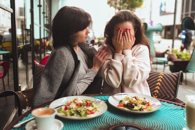 Vrouw die gezicht bedekt met handen en huilend naast haar moeder