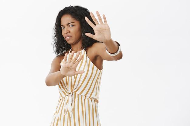 Vrouw die gezicht bedekt tegen flits ontevreden haat wordt gefotografeerd