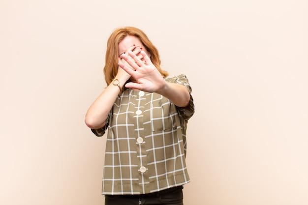 Vrouw die gezicht behandelt met hand en andere hand vooraan zet om camera tegen te houden, die foto's of beelden weigert