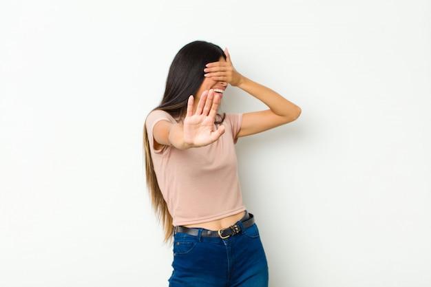 Vrouw die gezicht behandelt met hand en andere hand vooraan zet