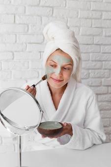 Vrouw die gezichtsbehandeling aanbrengt