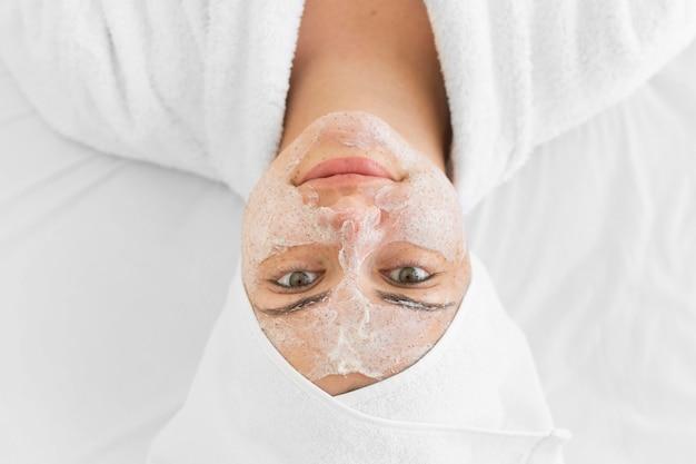 Vrouw die gezichtscrème bovenaanzicht draagt