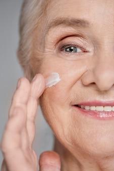 Vrouw die gezichtscrème gebruikt