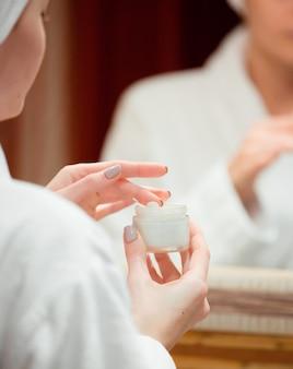 Vrouw die gezichtscrème met haar vinger in de badkamers neemt