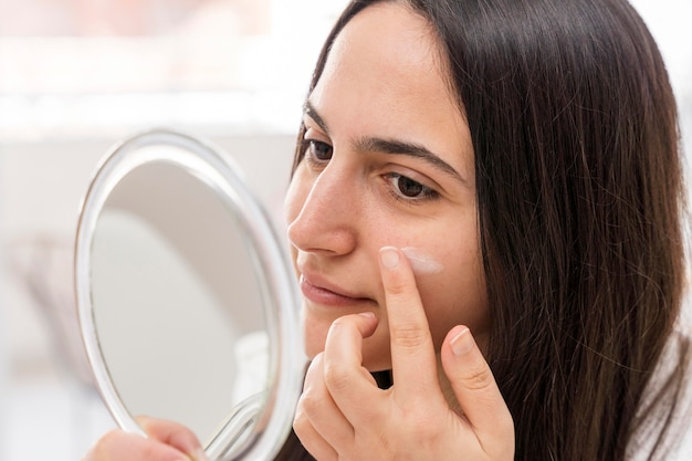 Vrouw die gezichtscrème toepast