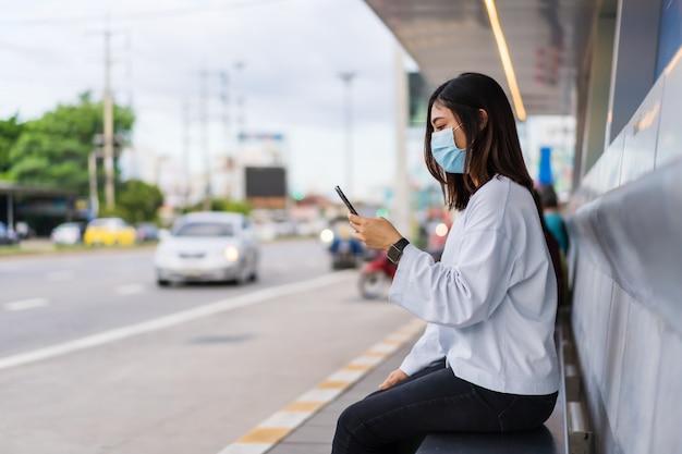 Vrouw die gezichtsmasker draagt beschermend voor coronavirus en smartphone gebruikt bij bushalte