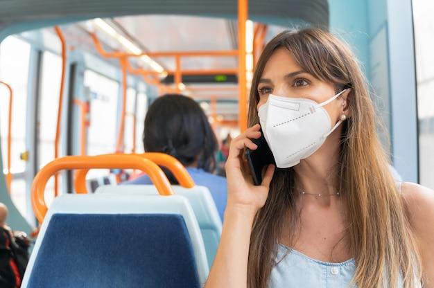 Vrouw die gezichtsmasker draagt dat aan de telefoon aan boord van de trein spreekt.