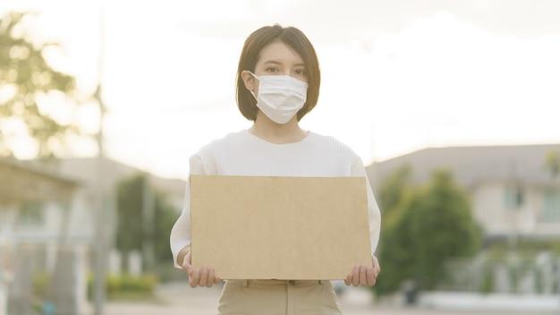 Vrouw die gezichtsmasker draagt dat een lege banner houdt om de tekst bij het protesteren te zetten.