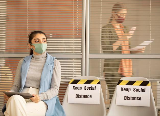 Vrouw die gezichtsmasker draagt dat een pauze neemt