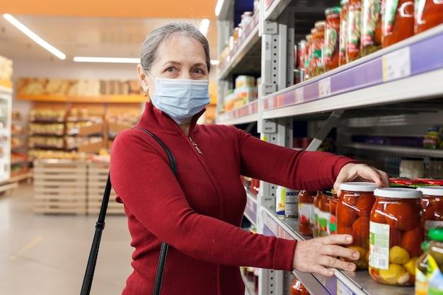 Vrouw die gezichtsmasker draagt dat en producten in supermarkt kiest