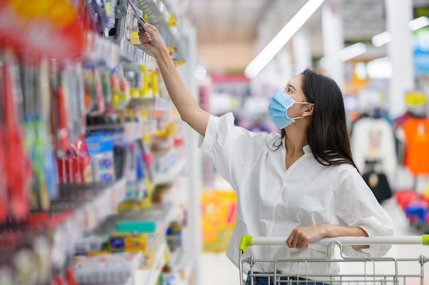 Vrouw die gezichtsmasker draagt dat in supermarkt koopt