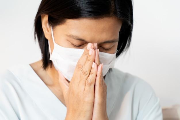Vrouw die gezichtsmasker draagt dat mond en neus behandelt terwijl het hoesten. ze bidt voor een einde aan het coronavirus-covid-19 dat de wereld in zijn greep houdt.
