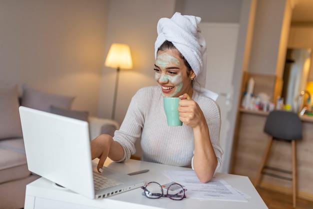 Vrouw die gezichtsmasker draagt dat thuis van geniet en haar laptop met behulp van.
