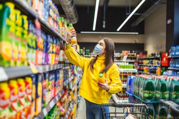 Vrouw die gezichtsmasker draagt die kruidenierswinkel in supermarkt koopt tijdens pandemie covid-19. vrouw met een winkelwagentje wat etenswaren in de supermarkt koopt.