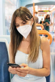 Vrouw die gezichtsmasker draagt die mobiele telefoon aan boord van trein gebruikt.