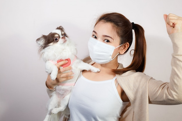 Vrouw die gezichtsmasker draagt en een hond hoding