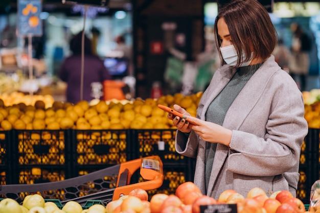 Vrouw die gezichtsmasker draagt en in kruidenierswinkelopslag winkelt