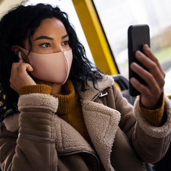 Vrouw die gezichtsmasker draagt in de bus tijdens het luisteren naar muziek in oordopjes