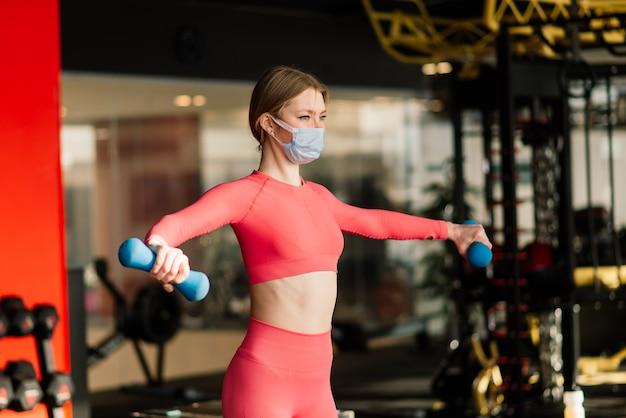 Vrouw die gezichtsmasker draagt, oefent training in de sportschool tijdens coronavirus pandermic, covid