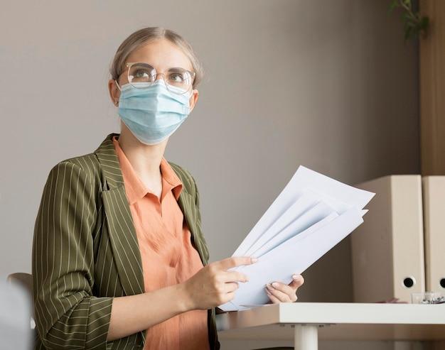 Vrouw die gezichtsmasker draagt op kantoor