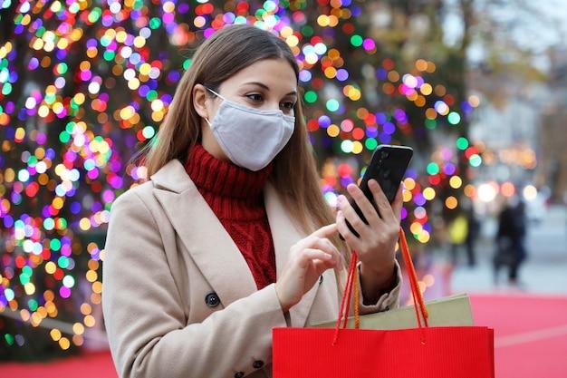 Vrouw die gezichtsmasker draagt op straat met boodschappentassen en slimme telefoon voor online aankopen met kleurrijke kerstboomverlichting