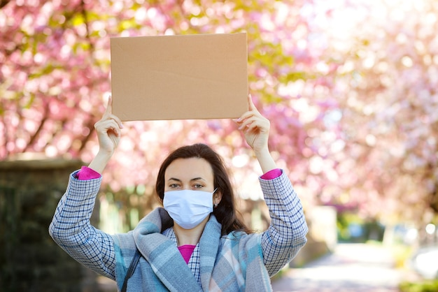 Vrouw die gezichtsmasker draagt tijdens quarantaine. vrouwelijke bedrijf leeg bord voor tekst buiten. coronapandemie.
