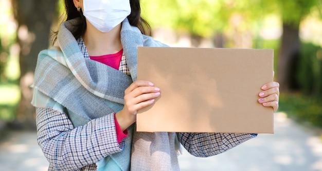 Vrouw die gezichtsmasker draagt tijdens quarantaine. vrouwelijke bedrijf leeg bord voor tekst buiten.