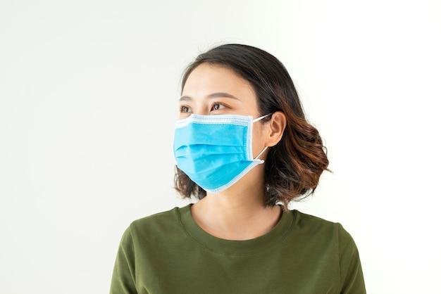 Vrouw die gezichtsmasker draagt vanwege luchtvervuiling of virusepidemie in de stad