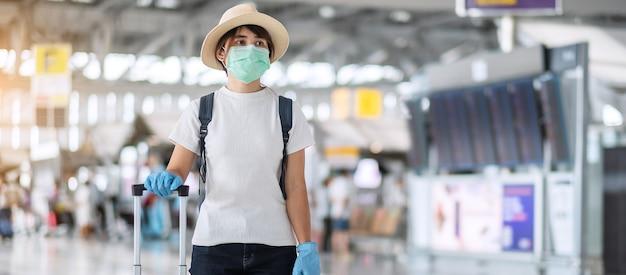 Vrouw die gezichtsmasker en nitrilhandschoen draagt ?? die handvatbagage in luchthaven houdt