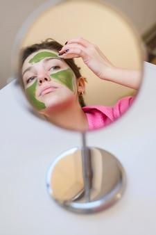 Vrouw die gezichtsmasker in de spiegel toepast