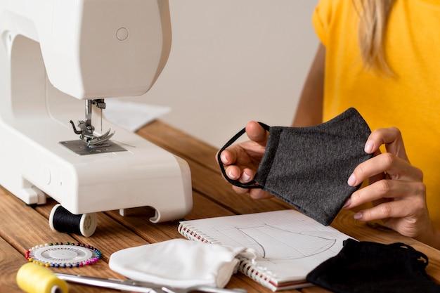 Vrouw die gezichtsmasker maakt met behulp van de naaimachine