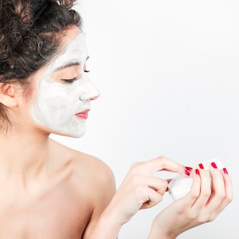 Vrouw die gezichtsmasker op haar gezicht toepast tegen witte achtergrond