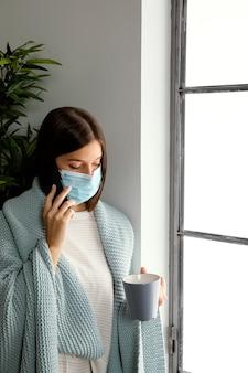 Vrouw die gezichtsmasker thuis draagt