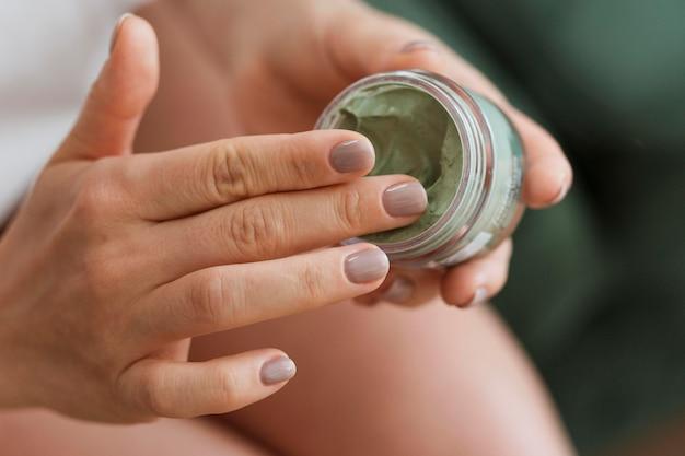 Vrouw die gezichtsmasker uit container