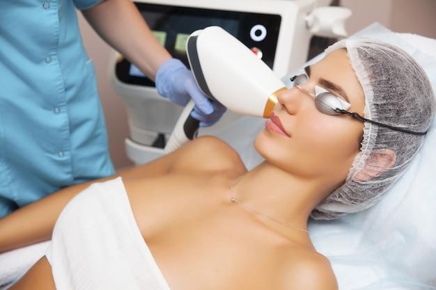 Vrouw die gezichtsschoonheidsbehandeling ontvangt, die pigmentatie verwijdert bij kosmetische kliniek.