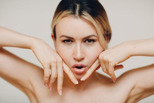 Vrouw die gezichtsyoga-massage maakt en verjongende oefeningen facebuilding