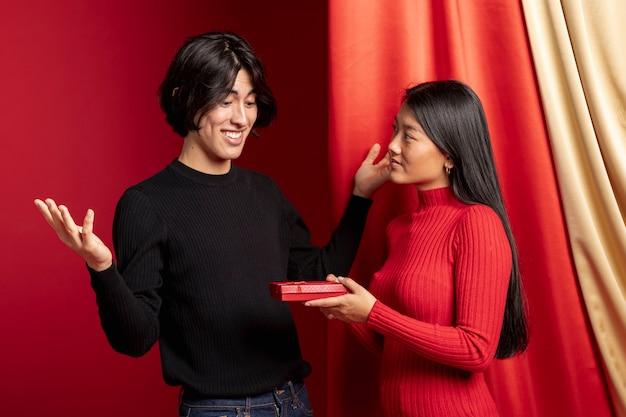 Vrouw die gift aanbiedt aan de mens voor chinees nieuw jaar