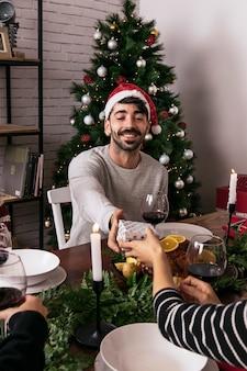 Vrouw die gift geeft aan vriend bij kerstmisdiner