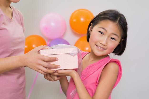 Vrouw die giftdoos geeft aan een klein meisje bij een verjaardagspartij