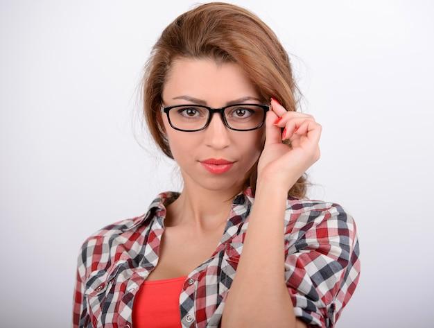 Vrouw die glazen aanpast en camera bekijkt.