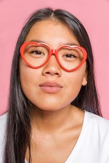 Vrouw die glazen draagt en camera bekijkt