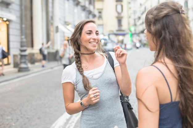 Vrouw die glimlachende vriend op straat bekijkt