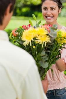 Vrouw die glimlacht aangezien zij met bloemen door haar vriend wordt voorgesteld