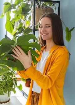 Vrouw die goed voor haar kamerplanten zorgt