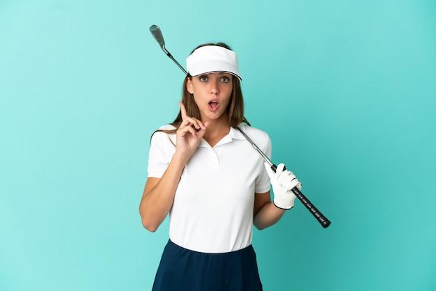Vrouw die golf speelt over een geïsoleerde blauwe achtergrond die van plan is de oplossing te realiseren terwijl ze een vinger opsteekt