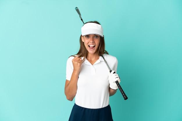 Vrouw die golf speelt over geïsoleerde blauwe achtergrond die een overwinning viert in winnaarspositie