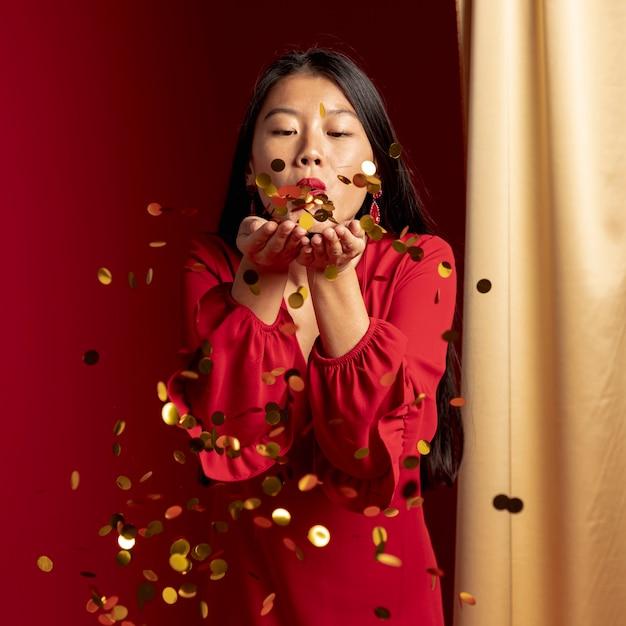 Vrouw die gouden confettien blaast