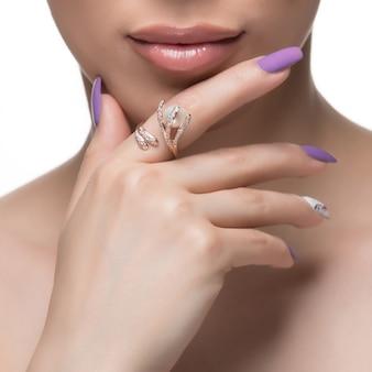 Vrouw die gouden ontwerpring in haar vinger bevordert.